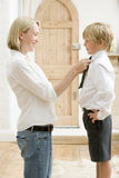 Woman in front hallway fixing young boy's tie and Royalty Free Stock Photos