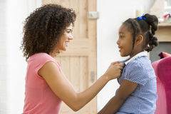 Woman in front hallway fixing young girl's dress a Royalty Free Stock Image