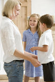 Woman in front hallway with two young children smi Royalty Free Stock Photo