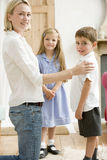 Woman in front hallway with two young children smi. Smiling woman in front hallway with two young children Stock Photo