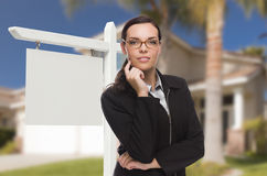 Woman In Front Of House and Blank Real Estate Sign Royalty Free Stock Images
