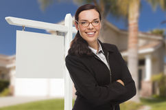 Woman In Front Of House and Blank Real Estate Sign Stock Photos