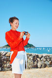 Woman in front of lagoon checking photos in digital camera Royalty Free Stock Photos