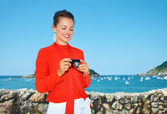 Woman in front of lagoon checking photos in digital camera Royalty Free Stock Photography