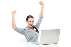 Woman in front of laptop with arms raised. Young woman over white background Royalty Free Stock Images