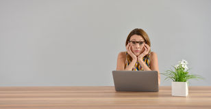 Woman in front of laptop getting tired. Woman in front of laptop with boring look, isolated Stock Photos