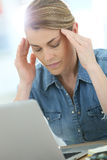 Woman in front of laptop having a headache. Woman in front of laptop suffering headache Royalty Free Stock Photos