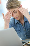 Woman in front of laptop having headache. Woman in front of laptop suffering headache Royalty Free Stock Images