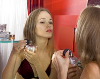 Woman in front of mirror Stock Images