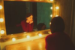 Woman in front of mirror in dressing room royalty free stock images