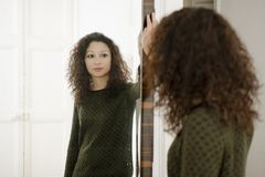Woman in front of a mirror. Latin woman in front of a mirror Royalty Free Stock Photo