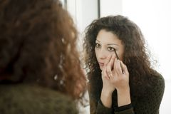 Woman in front of a mirror. Latin woman in front of a mirror, putting makeup on Stock Photo