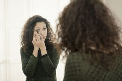 Woman in front of a mirror. Latin woman in front of a mirror, putting makeup on Stock Images