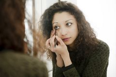 Woman in front of a mirror. Latin woman in front of a mirror, putting makeup on Royalty Free Stock Images