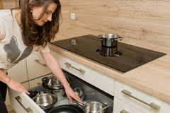 Woman in front of modern cooker with open drawer under the stove Royalty Free Stock Photos