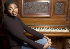 Woman in front of old piano. Beautiful black woman with old grand upright piano Royalty Free Stock Photos