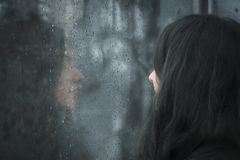 Woman in front of rainy window. Profile image of a young brunette woman with closed eyes thinking  in front of rainy window Stock Photo