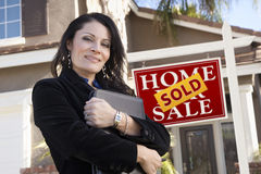 Woman in Front of Real Estate Sign and New Home Royalty Free Stock Photo