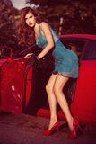 Woman in front red car. Attractive woman get out of car, retro look colors, small amount of grain added Royalty Free Stock Photos