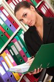 Woman in front of shelves with folders Royalty Free Stock Photography
