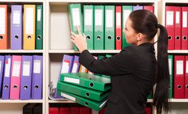 Woman in front of shelves with folders Stock Image