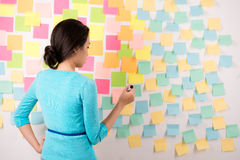 Woman in front of wall with many stickers Stock Photography