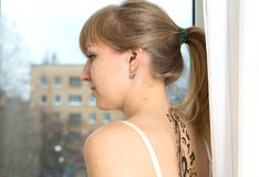 Woman in front of window. Beautiful girl with tattoo in front of window stock images