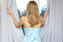 Woman in front of window. Beautiful girl with tattoo opening the blinds royalty free stock images