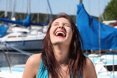 Woman in front of yacht boat is laughing. Stock Images