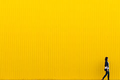 Woman in front of yellow wall Stock Photo