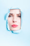 Woman frown face  thru blue ripped board Royalty Free Stock Photo