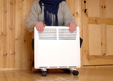 Woman froze and warms hands on white electric heater Royalty Free Stock Images