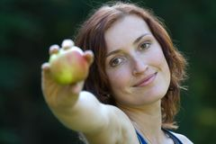 Woman and fruit. A young woman witch apple  in a park Royalty Free Stock Photo