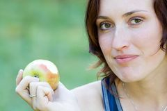 Woman and fruit. A young woman witch apple  in a park Stock Image