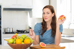 Woman with fruit bowl on counter in kitchen Royalty Free Stock Image