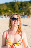 Woman with fruit cocktail relaxing on beach Stock Photos