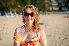 Woman with fruit cocktail relaxing on beach Royalty Free Stock Image