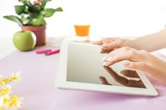Woman and fruit diet while working on computer in office. Female hands holding tablet. Side view on woman. Trendy color pink desk. Woman, stilish workplace. Pc Stock Image