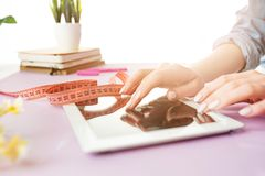 Woman and fruit diet while working on computer in office. Woman, healthy eating. She working on computer in office. Female hands holding tape. Side view on woman Stock Image