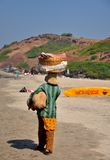 Woman fruit seller at beach. This image describes a woman fruit seller selling their fruits at beach at Goa, india. In india, population below poverty line has Stock Photos
