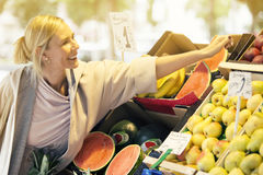 Woman at a fruit stand picking fruits Royalty Free Stock Images