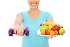 Woman with fruits and dumb-bells Stock Photo