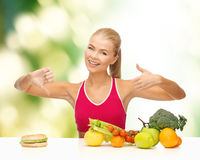 Woman with fruits and hamburger comparing food stock images