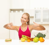Woman with fruits and hamburger comparing food Stock Photos