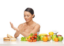 Woman with fruits rejecting hamburger Stock Image