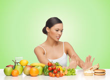 Woman with fruits rejecting hamburger. People, junk food, healthy eating, diet and weight loss concept - woman with fruits and vegetables rejecting hamburger Royalty Free Stock Image