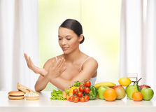 Woman with fruits rejecting junk food stock image