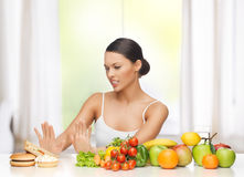 Woman with fruits rejecting junk food Royalty Free Stock Photo