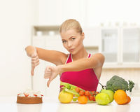 Woman with fruits showing thumbs down to cake Royalty Free Stock Image