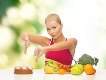 Woman with fruits showing thumbs down to cake Stock Images